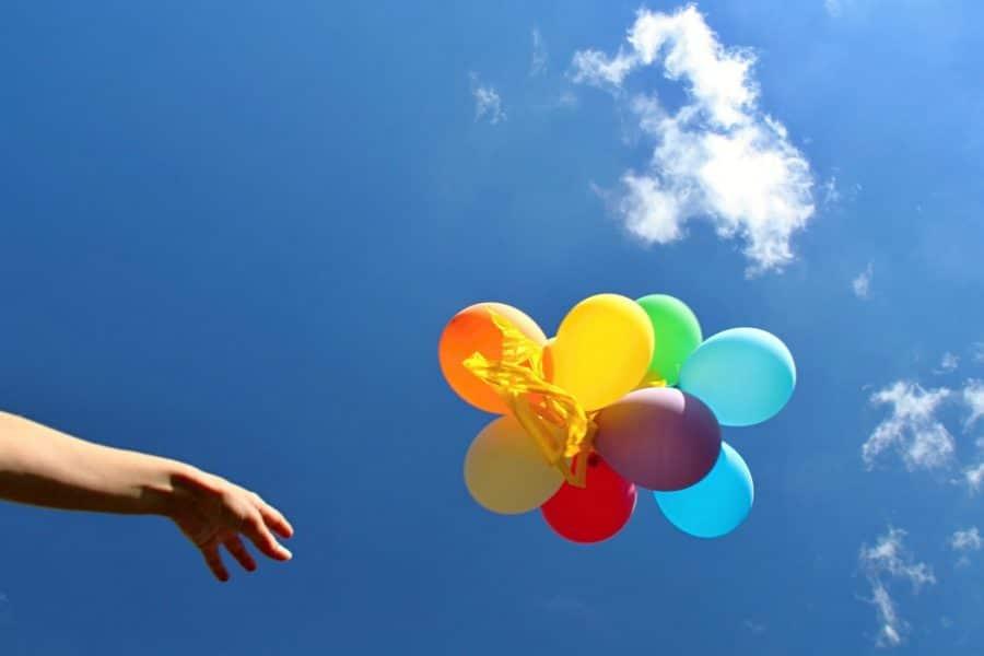 человек отпускает шарики в небо